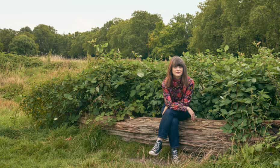 Kat Lister sitting on a log in a field