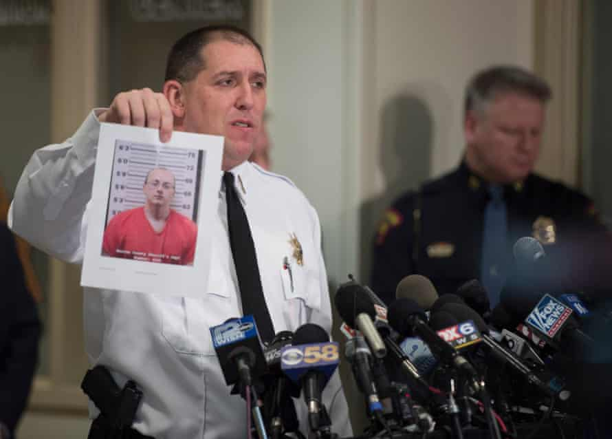 The Baron county sheriff holds up a photo of the suspect, Jake Thomas Patterson.