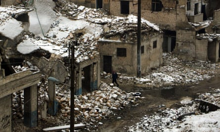 A Syrian man walks past damaged home in Aleppo  following a snow storm on 5 January 2016