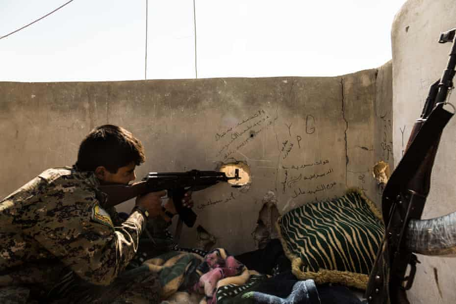 An SDF fighter checks for enemy movements from a sniper position overlooking Isis-held areas.