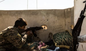 A Syrian Democratic Forces (SDF) fighter checks for enemy movements during the liberation of Raqqa from Isis.