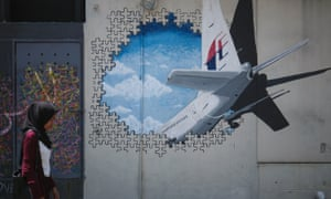 A woman walks past graffiti of the missing Malaysia Airlines flight MH370 in Kuala Lumpur, Malaysia. The plane disappeared on 8 March 2014.