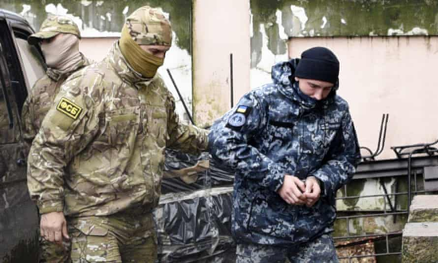 A Ukrainian sailor is escorted by a Russian intelligence officer to a court room in Simferopol, Crimea, on Tuesday.