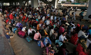 Migrant workers and their families wait for transport to a railway station to board a train to their home state of northern Uttar Pradesh, after a limited reopening of India's rail network following a nearly seven-week lockdown to slow the spreading of the coronavirus in Ahmedabad, India.