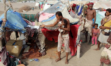 People displaced by the war in Yemen's west coast areas gather outside their tent at a camp near Aden, Yemen, on 27 May 27.