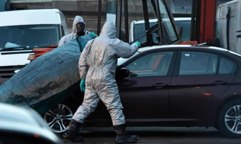 Forensic officers in hazmat suits examine the BMW belonging to Sergei Skripal in Salisbury, England.