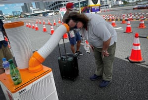 Cooling off in front of a portable air conditioner while waiting for a bus at the Tokyo Games' main transport mall.