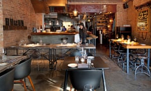 The dining room of 108 Garage restaurant, with brick walls and low lighting