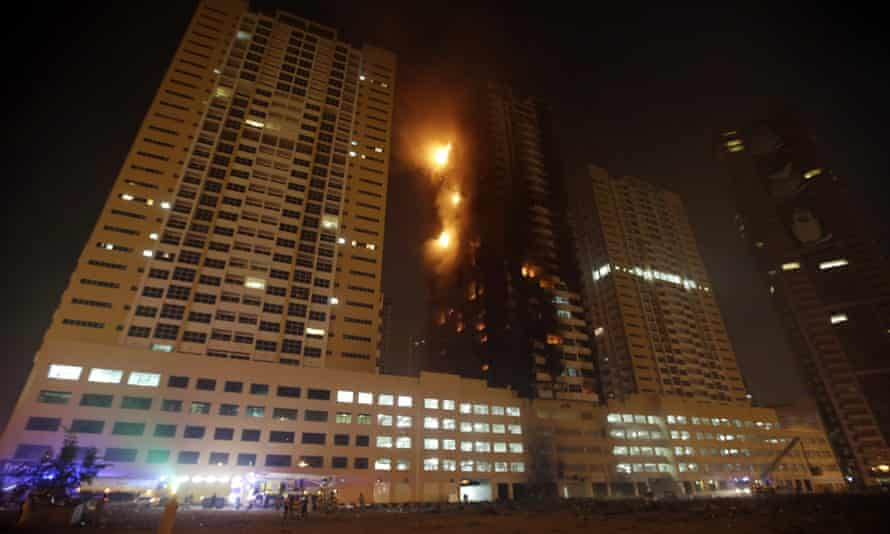 Members of the Civil Defense and fire services try to extinguish a fire at residential buildings at al-Sawan area in the Gulf emirate of Ajman.