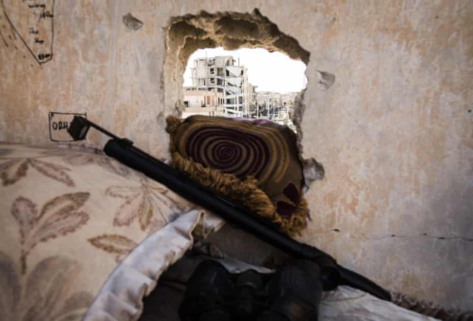 Destroyed buildings are seen through a sniper position overlooking Isis-held areas.
