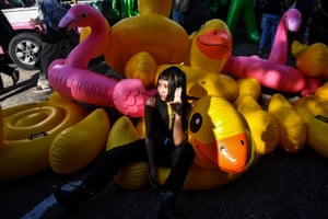 A pro-democracy protester gives the three-finger salute as she poses on an inflatable duck