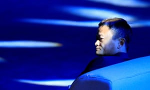 Jack Ma photographed in profile siting on a settee, his face partially illuminated by rays of pale blue light