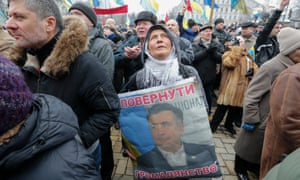 A protester holds a portrait of Mikheil Saakashvil during the rally in central Kiev