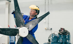 A young woman is working on a wind turbine in an engineering workshop. She is wearing a protective mask as well as blue coveralls.