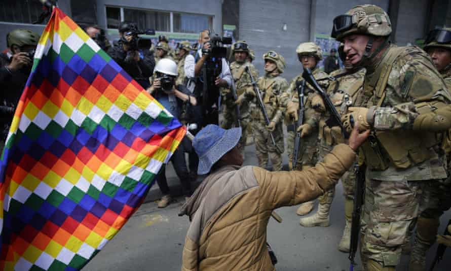 A supporter of Evo Morales talks with a member of the Bolivian army at a protest against the provisional government in La Paz, Bolivia.