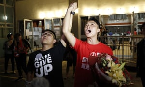 Pro-democracy candidate Jimmy Sham, right, celebrates with a supporter after winning his electoral battle in Hong Kong.