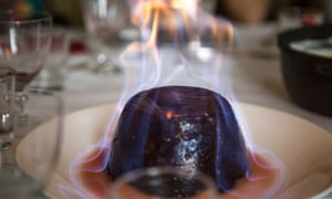 A Christmas pudding in flames on a dinner table.