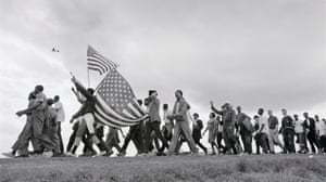 Marchers in Alabama cross the horizon on the march from Selma to Montgomery on 21 March 1963. A reconnaissance plane of the Alabama National Guard, drafted in to protect the march, flies above them