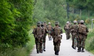 Troops patrol the Nationaal Park Hoge Kempen in Maasmechelen on June 4 as part of the manhunt for Jurgen Conings, a fugitive Belgian soldier.