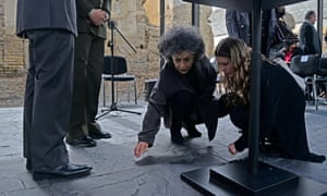 Doris Salcedo cleans a spill on the floor during the pre-inauguration of her peace monument titled Fragmentos (Fragments).