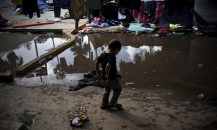 A Honduran boy plays next to the flooded area at a migrant shelter in Tijuana, Mexico.