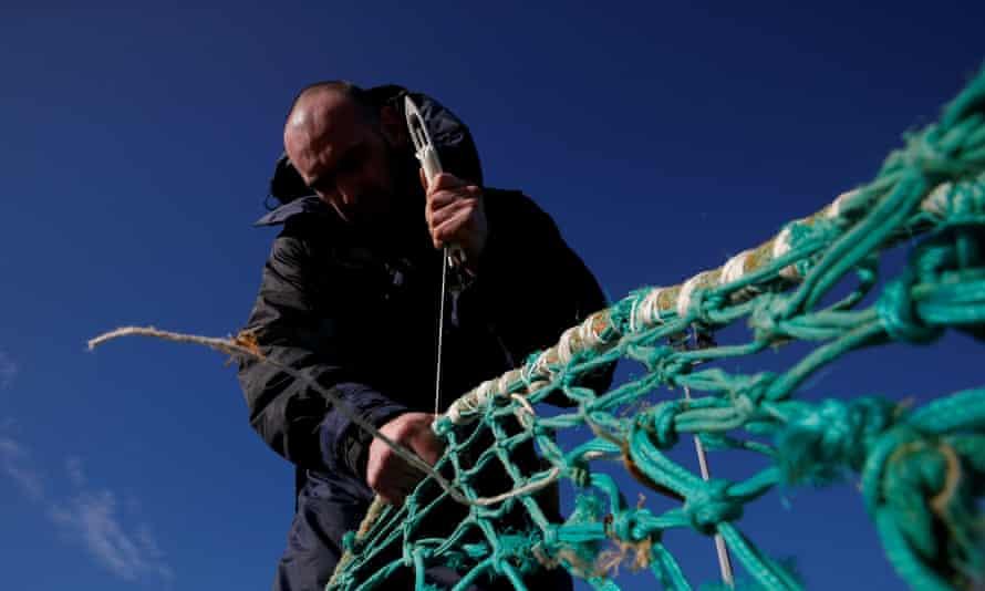 Fisherman repairs net