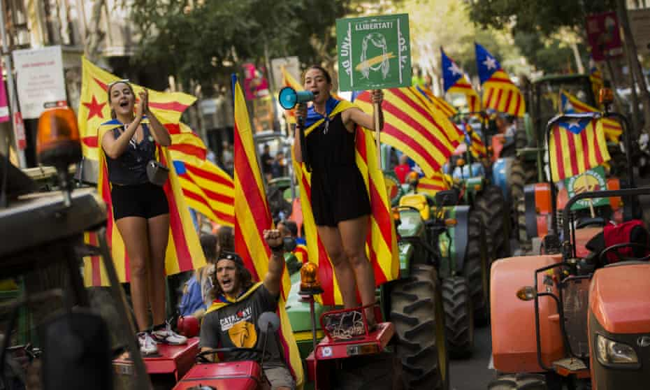 People with the Catalan independence flag on top of parked tractors during a protest by farmers in Barcelona.