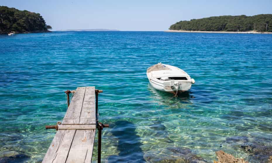 Crystal blue sea boat and jetty at Cikat Bay, Losinj