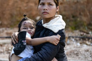 Quang Nam, Vietnam – Ho Thi Ha carries her injured daughter after she was rescued from a landslide