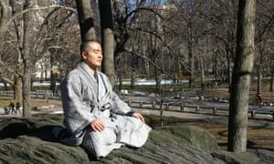 Haemin Sunim sitting cross-legged, meditating, in a park wearing a grey robe