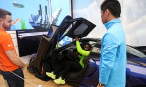 Employees try out a McLaren Senna car simulator before the Microsoft store's opening.