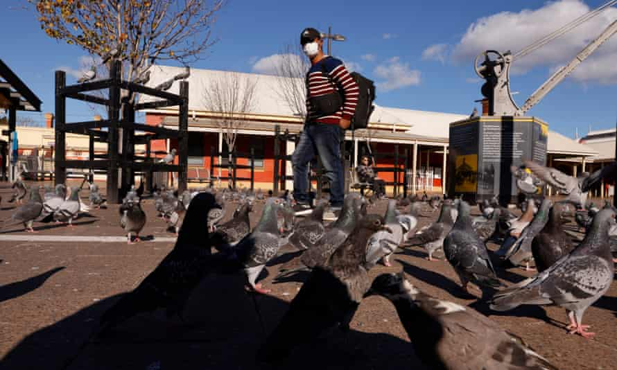 A man walks past pigeons at Fairfield Station on Sunday as the NSW government relaxed some restrictions for Sydney's south-west just a day after tightening them.