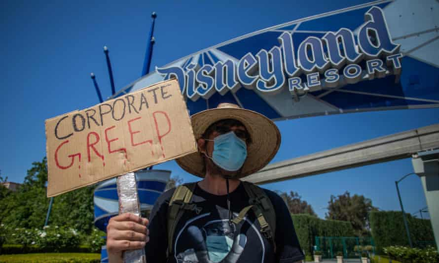 A man part of the coalition of resort labor unions holds a sign in front of Disneyland Resort in Anaheim, California, calling for higher safety standards before its reopening last Friday.