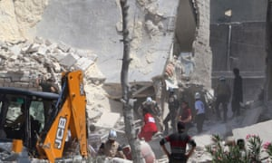Syrian Civil Defence members work at a site hit by an airstrike in Marjeh in June.