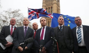 Anti-Brexit protesters hold flags as Nigel Dodds speaks outside parliament, flanked by other DUP MPs.