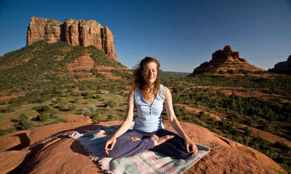 A woman meditating at a vortex site in Sedona, Arizona, US.