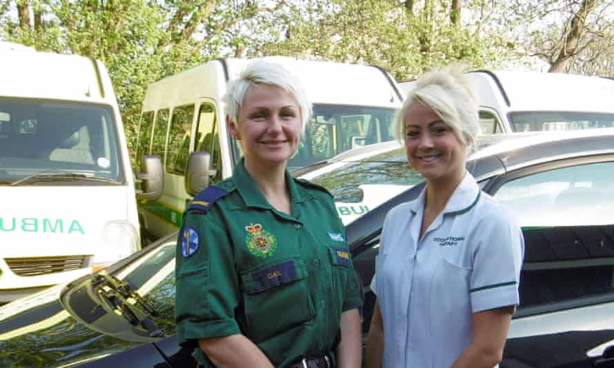 Occupational therapist with paramedic in front of ambulances