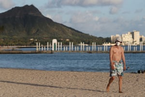 A beachgoer wearing a protective mask in Honolulu, Hawaii. The state has maintained some of the lowest levels of Covid-19.