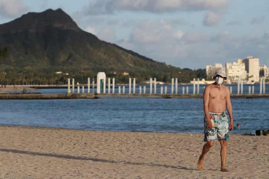 A beachgoer wears a mask on Waikiki beach in Hawaii, with Diamond Head mountain in the background.