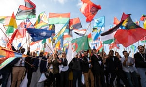 People waving flags at the opening ceremony of One Young World 2018.