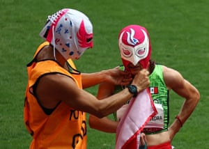 Moníca Olivia Rodríguez Saavedra of Mexico and guide Kevin Teodoro Aguilar Perez wearing luchador masks as they celebrate winning gold and setting a new world record in the women's 1500m T11 final.