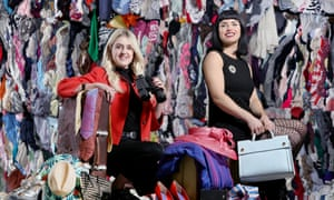 Oxfam staff pictured next to huge bales of clothing