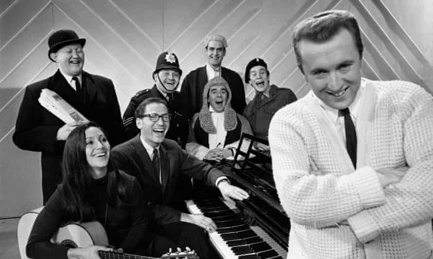 Julie Felix with the Frost Report team in 1966, rear from left, Nicholas Smith, Ronnie Barker, John Cleese and Nicky Henson, and front, from left, Tom Lehrer, Ronnie Corbett and David Frost.