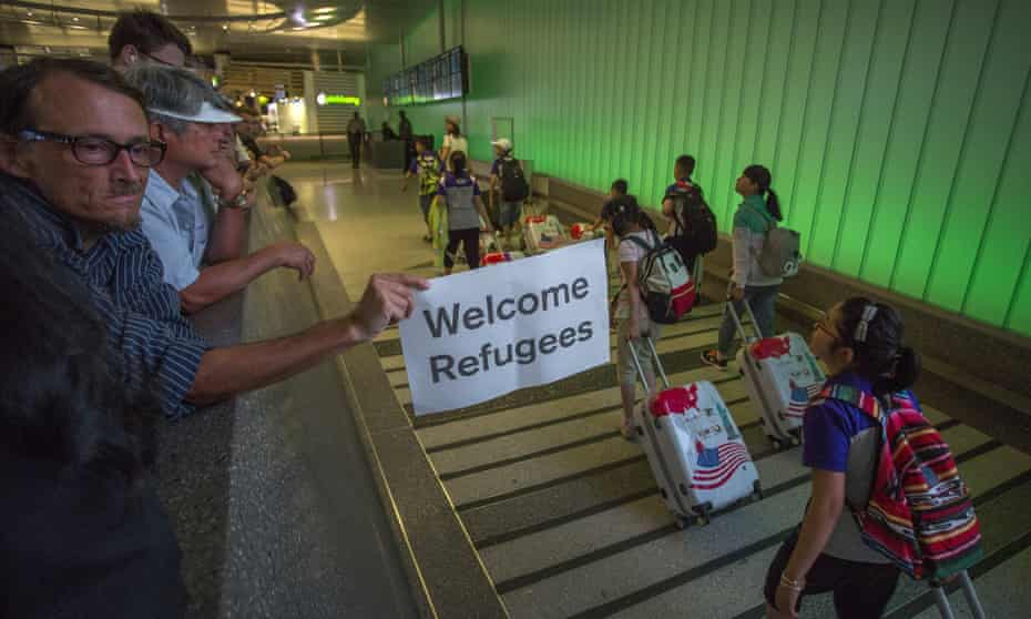 A man displays a welcome sign near arriving travellers on the first day of the partial reinstatement of the Trump travel ban in Los Angeles on 29 June 2017.