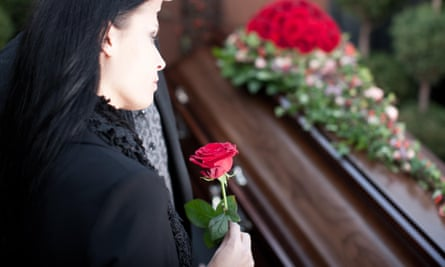 A woman standing over a coffin with a rose in her hand