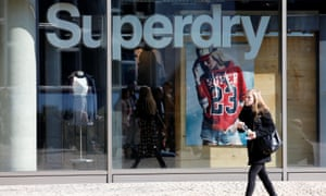 A woman walks past a Superdry fashion store in Berlin