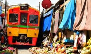 A train passes through the Maeklong market