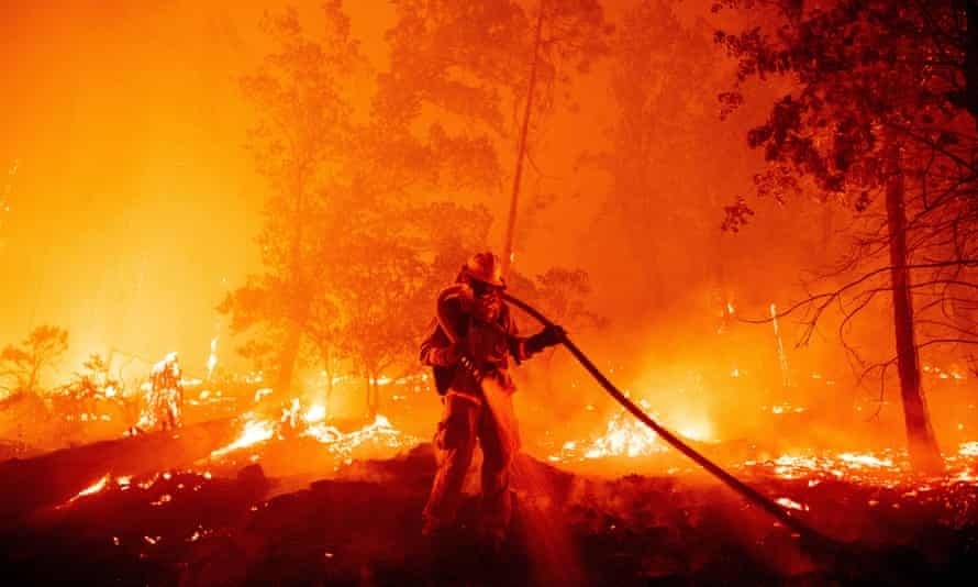 A firefighter douses flames as they push towards homes during the Creek fire in the Cascadel Woods area of unincorporated Madera County, California