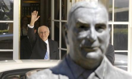 John Howard waves behind a bust of Sir Robert Menzies
