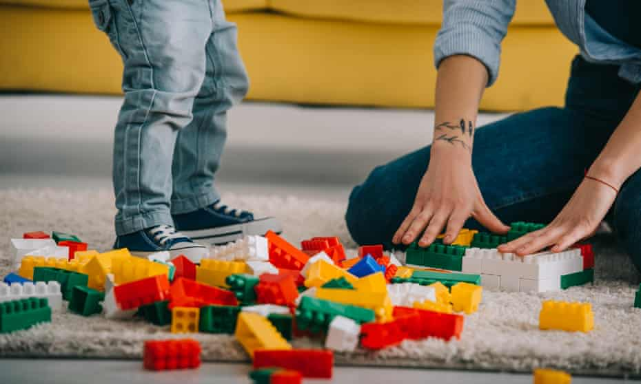 child and parent playing with lego